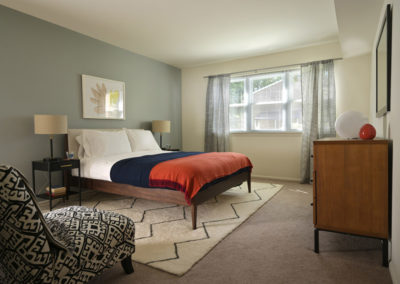 Furnished master bedroom with large windows in Radwyn Apartments