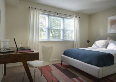 Furnished guest bedroom with large windows in Bryn Mawr apartment