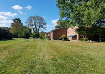 Wide shot of Radwyn with pictureque apartment rentals and fields on beautiful day in Bryn Mawr, PA